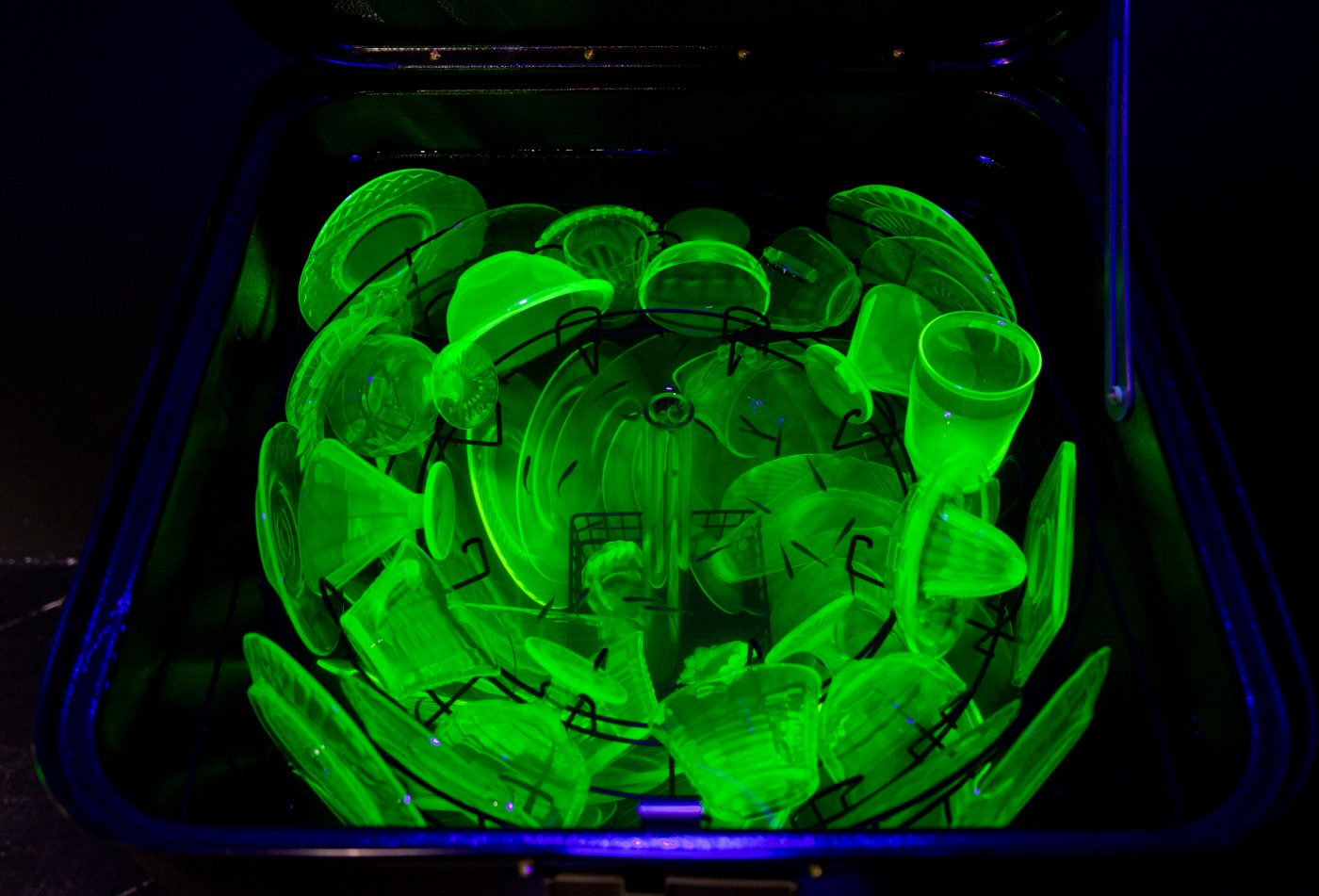 NATURE THEATER OF VIOLENT SUCCESSION  Cold War Dishwasher (Uranium Glass)</I>, 2015 (detail) Vintage refurbished Kenmore dishwasher, assorted uranium glass dishware, live freshwater ecosystem, sump tank, biological filter pump, crushed glass substrate, Danionin sp. fish, blacklight hood lamp 
